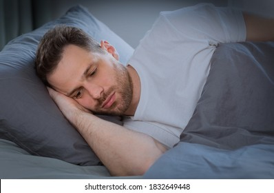 Depressed Man Having Insomnia Unable To Sleep Lying In Bed In Bedroom At Home At Night. Sleeplessness, Mental Health Problem, Male Depression Concept. Low Light