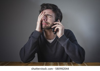 Depressed man hearing bad news over his cell phone