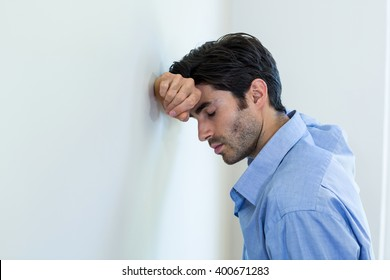 Depressed man leaning his head against a wall at home