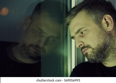 Depressed man looking sadly through the window
