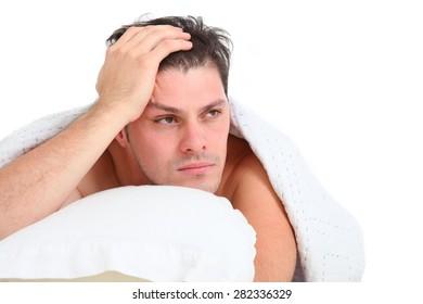 depressed man lying in bed