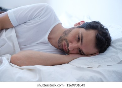 Depressed man lying in his bed and feeling worried