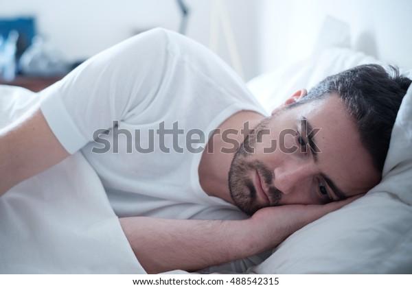 落ち込んだ男がベッドに横たわり、気分が悪くなった