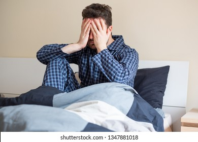 Depressed man portrait sitting on the bed