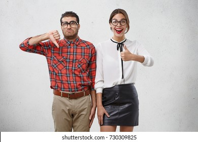 Depressed man shows dislike sign, being tired of work, looks unhappily stands near woman with happy expression, have opposite reaction on proposal. Emotional weird couple express different opinion