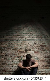 Depressed man sitting alone against brick wall.
