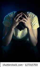 Depressed man sitting in the dark