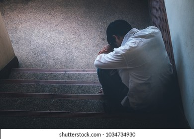 Depressed man sitting head in hands on the stairs in building. with low light environment, dramatic concept, concept of Major depressive disorder, unemployed, sadness, depressed and human problems,
