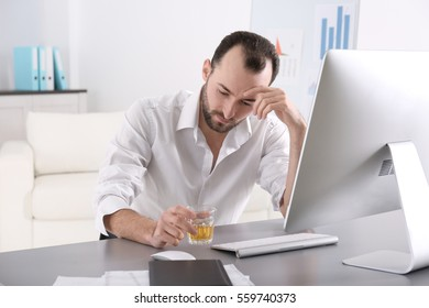 Depressed man sitting in office with glass of whisky
