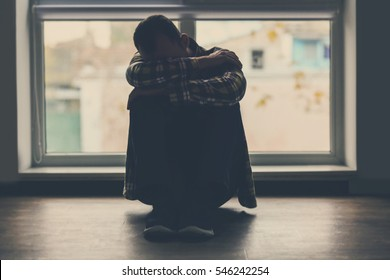 Depressed man sitting on floor near window