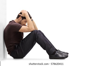 Depressed man sitting on the floor with his head down and leaning against a wall isolated on white background