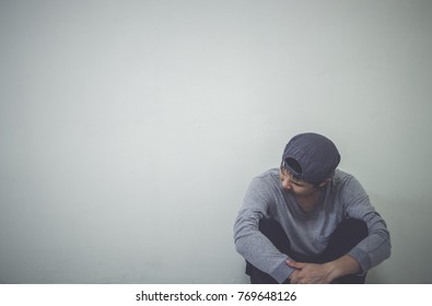 Depressed man sitting on floor in an empty room , This is major depressive disorder.