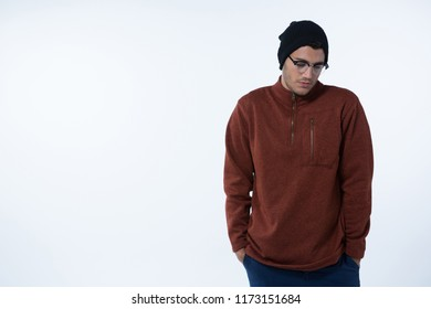 Depressed man standing against white background