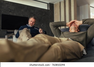 Depressed man visiting psychologist for consultation. Male patient lying on couch with psychotherapist making notes.