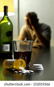 Depressed man with wine and prescription pills, vertical