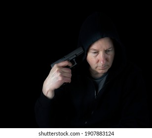 Depressed mature man ready to commit suicide with gun pointed to side of head while surrounded in darkness