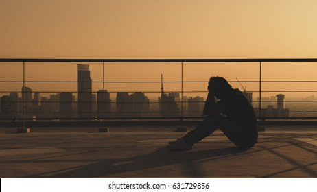 Depressed or mentally ill man sit on top of building with city scape in background. Warm color tone with copy space.