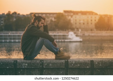 Depressed modern businessman sitting by the river.Toned image.