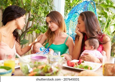 Depressed Mother With Baby Talking To Friends