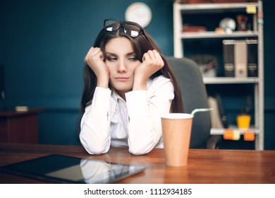 Depressed office assistant sitting with her head resting on her hands. Weary tired business lady with glasses on her head sitting in loneliness at table with coffee cup and tablet on desktop.