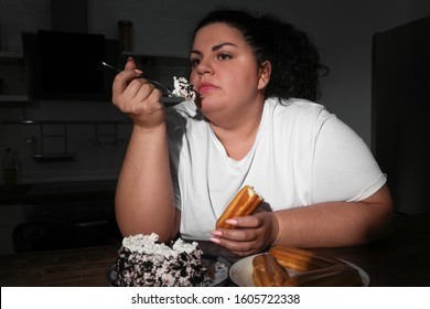 Depressed overweight woman eating sweets in kitchen at night