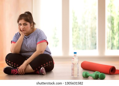 Depressed overweight woman sitting on the floor and doesn't wont to exercise