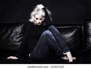 depressed platinum blonde woman on sofa. The sofa and walls are dark to reflect her state of mind.
