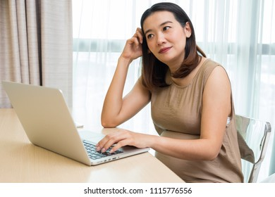 Depressed pregnant asian woman working on laptop.