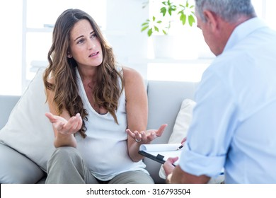 Depressed pregnant woman talking with psychiatrist in clinic