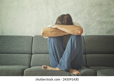 Depressed and sad man on the couch in the room, covering face and crying in despair