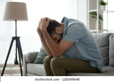 Depressed sad man in trouble sitting on couch holding head in hands feeling pain lonely heartbroken upset worried hopeless, stressed desperate guy loser having problems, grieving, regrets of mistake
