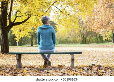 Depressed and sad old woman on bench in autumn park, from back angle