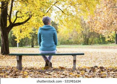 Depressive und traurige alte Frau auf Bank im Herbstpark, aus Rückenwinkel