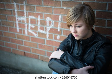 Depressed, sad teen girl sits outside school wall, asking for help