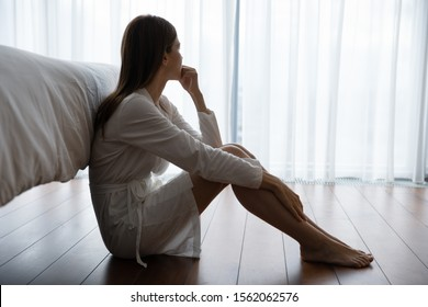 Depressed sad worried young woman wear night gown sit on bedroom floor alone troubled with loneliness, upset about solitude mental problem look at window think of abortion regret bad mistake concept
