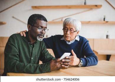 depressed senior friends looking at smartphone in cafe