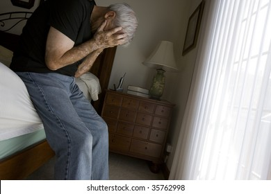 Depressed senior man in bedroom setting with natural light.