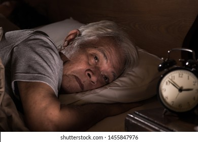 Depressed senior man lying in bed cannot sleep from insomnia