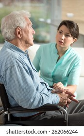 Depressed senior man using wheelchair talking with nurse