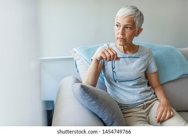 Depressed senior woman near window at home. Lonely senior woman. Pensive woman. Sad Mature Woman Suffering From Agoraphobia Looking Out Of Window.