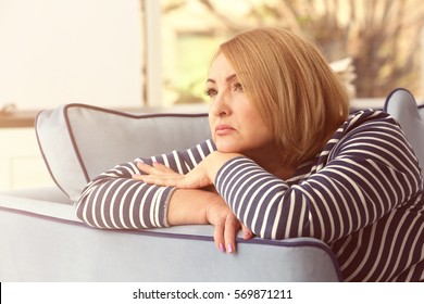 Depressed senior woman sitting on sofa at home