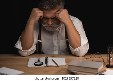 depressed senior writer sitting at workplace with blank manuscript