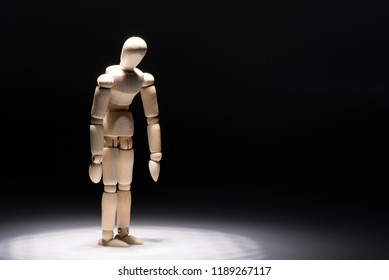 Depressed standing wooden doll under a spotlight in front of dark background