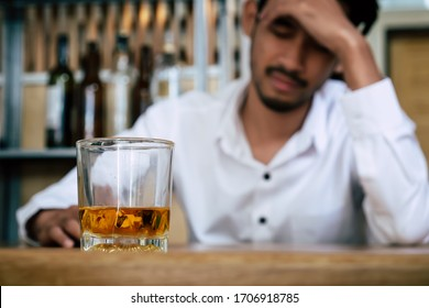 Depressed stressed and lonely man sitting in the dark facing with unemployment financial crisis and family divorce or personal problem and sadness with a glass of whiskey, alcoholic, alcohol addiction