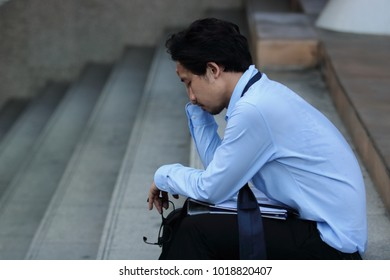 Depressed stressed young Asian business man feeling strain or tried or disappointed at staircase.