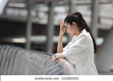 Depressed stressed young Asian business woman with hands of face suffering from trouble