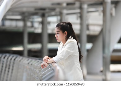 Depressed stressed young Asian business woman suffering from trouble at outside office.