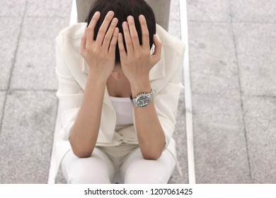Depressed stressed young Asian business woman covering face with hands suffering from trouble