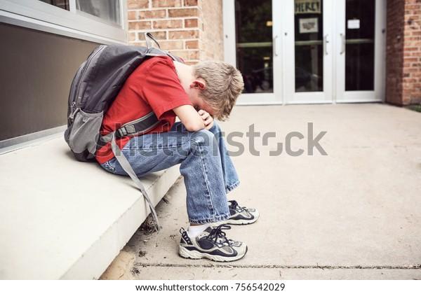 Depressieve student zit buiten school zijn gezicht te verbergen