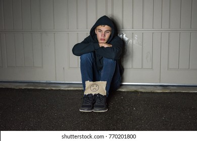 A depressed teen boy holding a sad face sign in front of a garage door.